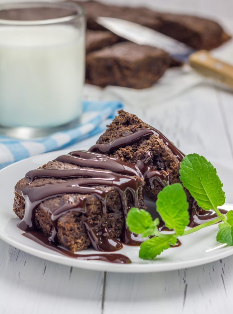 Homemade brownies with chocolate sauce and glass of milk